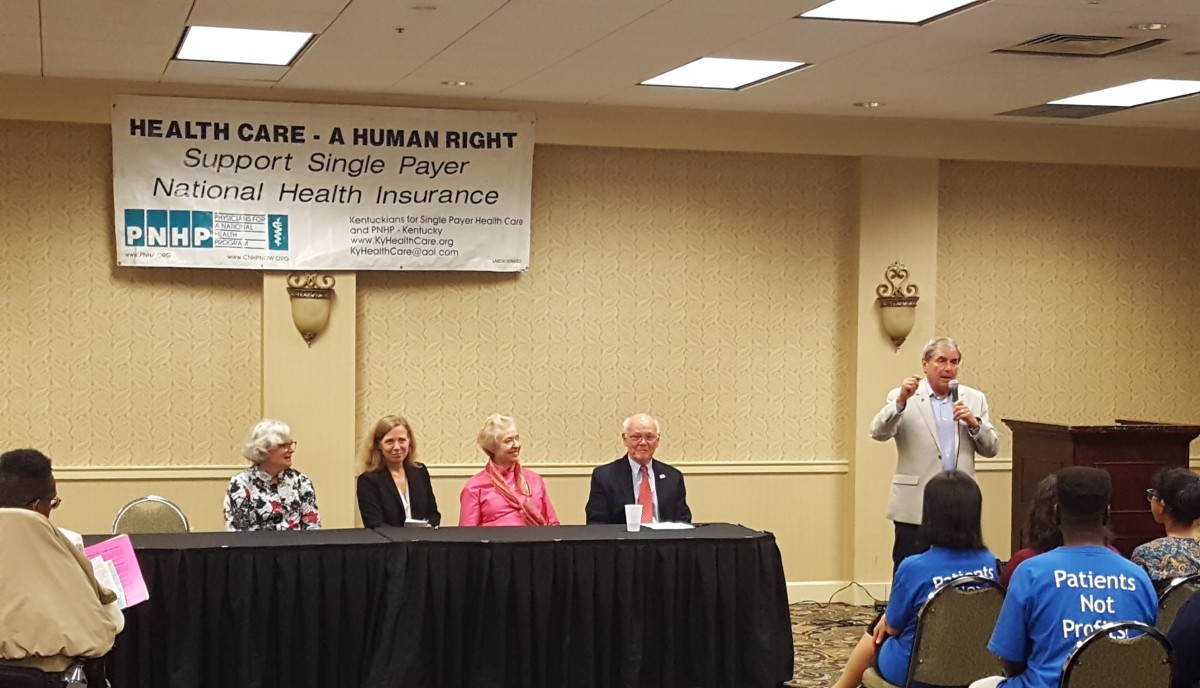Congressman John Yarmuth, a cosponsor of HR 676, speaking at the October 4 public event. Seated (l to r) are Dr. Carol Paris, President of Physicians for a National Health Program, Dr. Margaret Flowers, Kay Tillow, Chair, Kentuckians for Single Payer Health Care, and Dr. Garrett Adams, Founder of Physicians for a National Health Program-Kentucky. Not pictured is Ann Hagan-Grigsby, CEO of Park DuValle Community Health Center who also spoke.