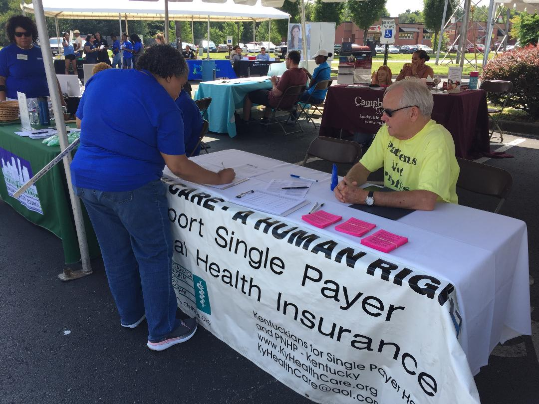 A supporter signs the petition for National Improved Medicare for All as Charlie Casper staffs the single payer booth.